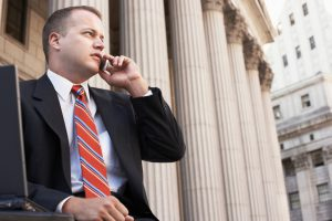 Businessman using mobile phone outside courthouse